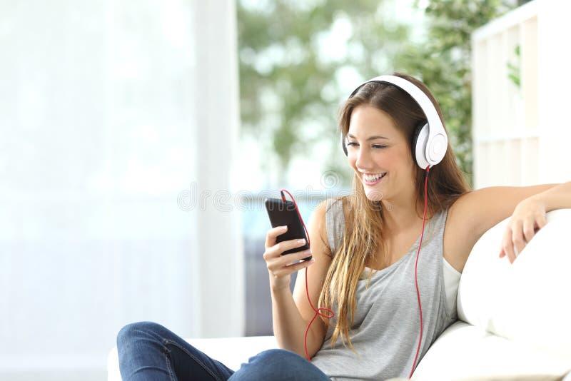 Gelukkig meisje die aan muziek van mobiele telefoon luisteren stock afbeelding