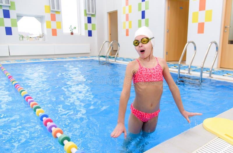 Gelukkig meisje die in de pool zwemmen Het Kaukasische kind speelt pret in de kleuterschoolpool stock afbeeldingen