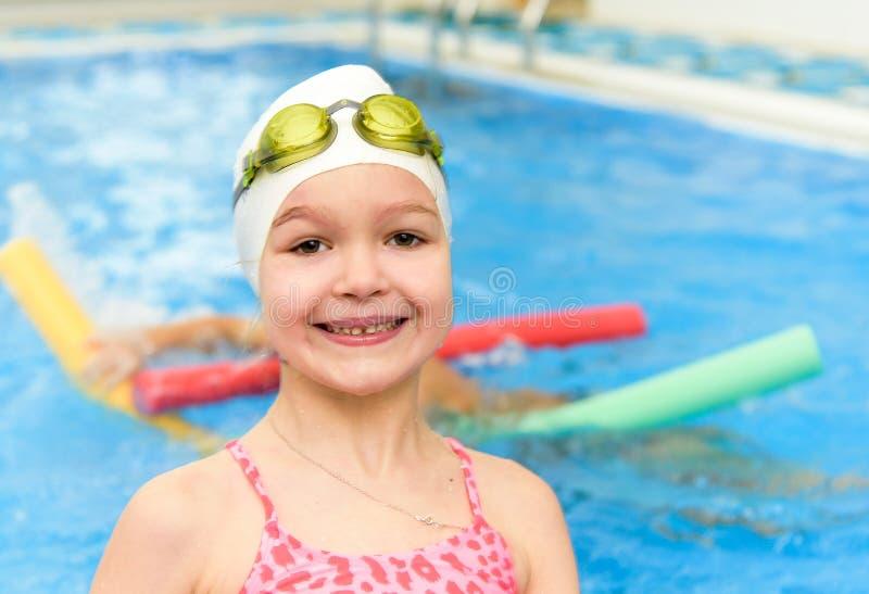Gelukkig meisje die in de pool zwemmen Het Kaukasische kind speelt pret in de kleuterschoolpool stock fotografie