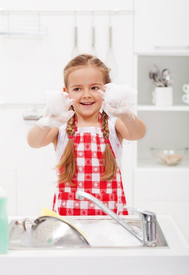 Gelukkig meisje die de schotels wassen stock foto's