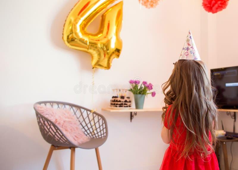 Gelukkig meisje die de vierde verjaardag thuis vieren stock foto's