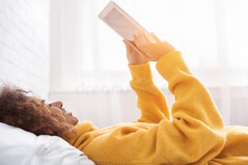Gelukkig meisje die digitale tablet gebruiken, die in bed liggen stock foto