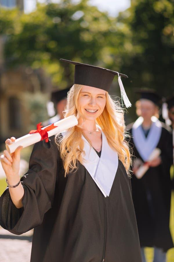 Gelukkig meisje die diploma tonen aan haar vrienden royalty-vrije stock foto's