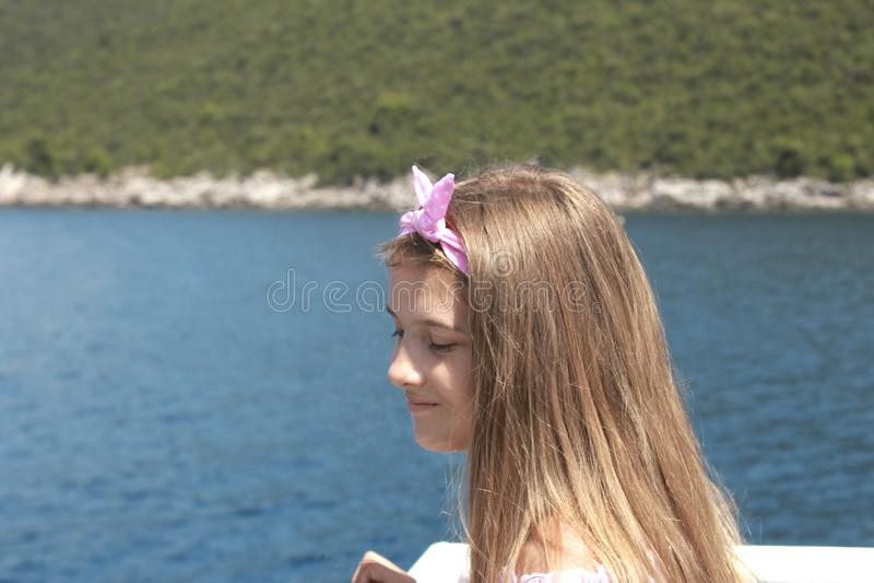 Gelukkig meisje die in een boot varen die bij het overzees op de zomercruise glimlachen stock afbeeldingen