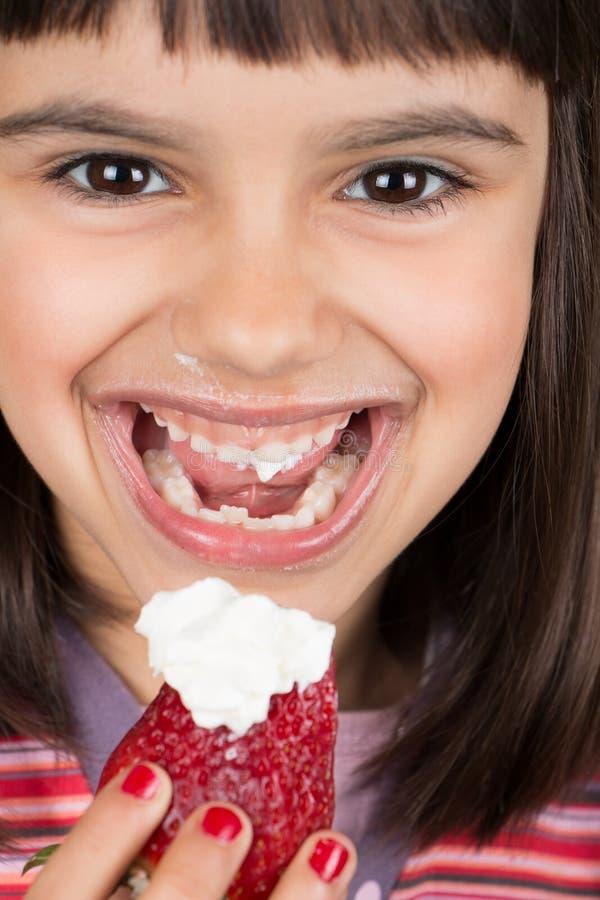 Gelukkig meisje die een grote aardbei met room eten stock foto's