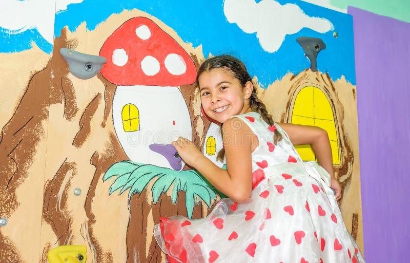 Gelukkig meisje die een rotsmuur beklimmen binnen stock fotografie