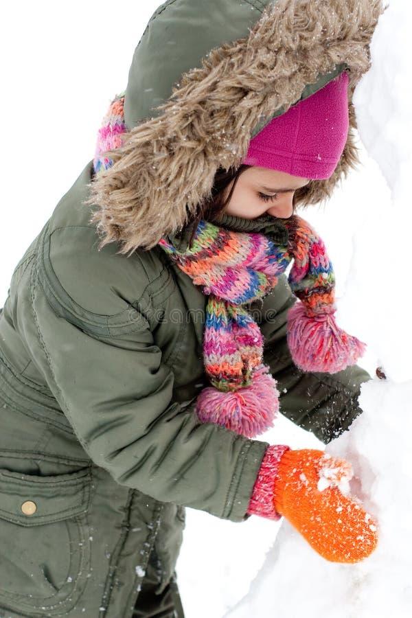 Gelukkig meisje die een sneeuwman maken stock foto's