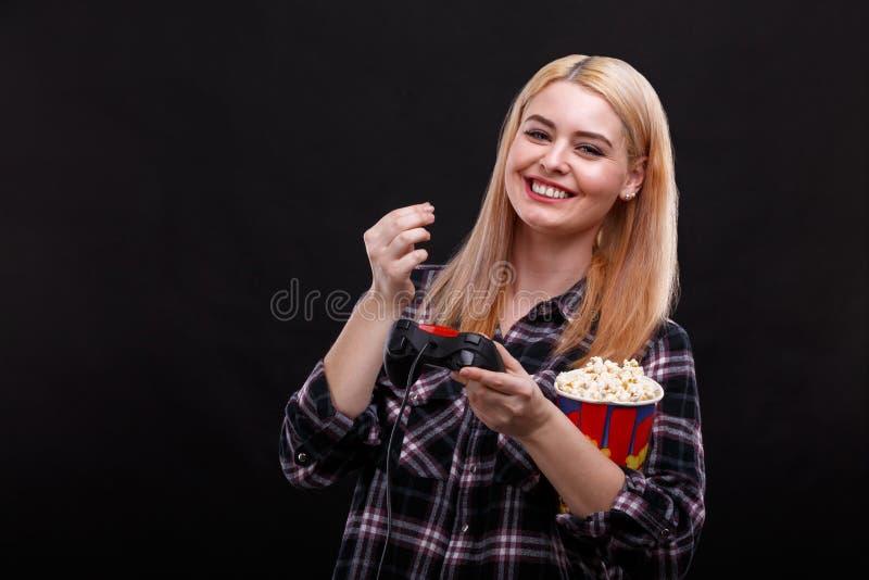 Gelukkig meisje die een spelconsole houden en popcorn eten stock fotografie