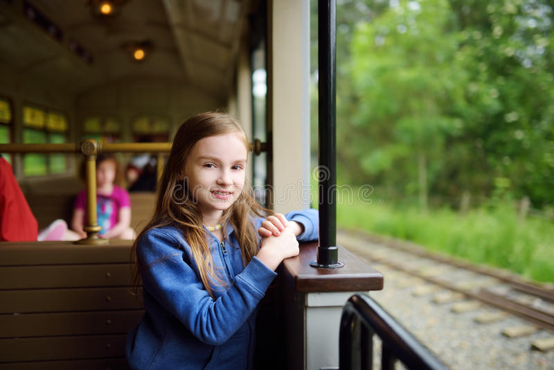 Gelukkig meisje die een trein in een themapark berijden of funfair stock afbeeldingen