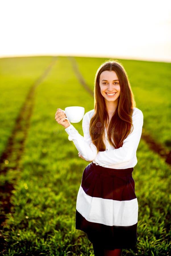 Gelukkig meisje die en het drinken koffiethee glimlachen royalty-vrije stock fotografie