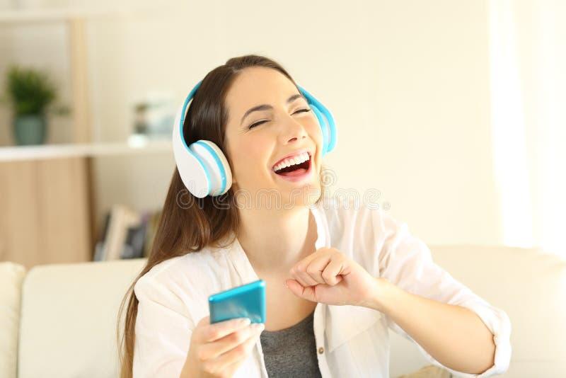 Gelukkig meisje die en het zingen aan muziek dansen luisteren royalty-vrije stock afbeelding