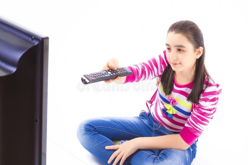 Gelukkig meisje die en op TV bepalen letten royalty-vrije stock afbeelding