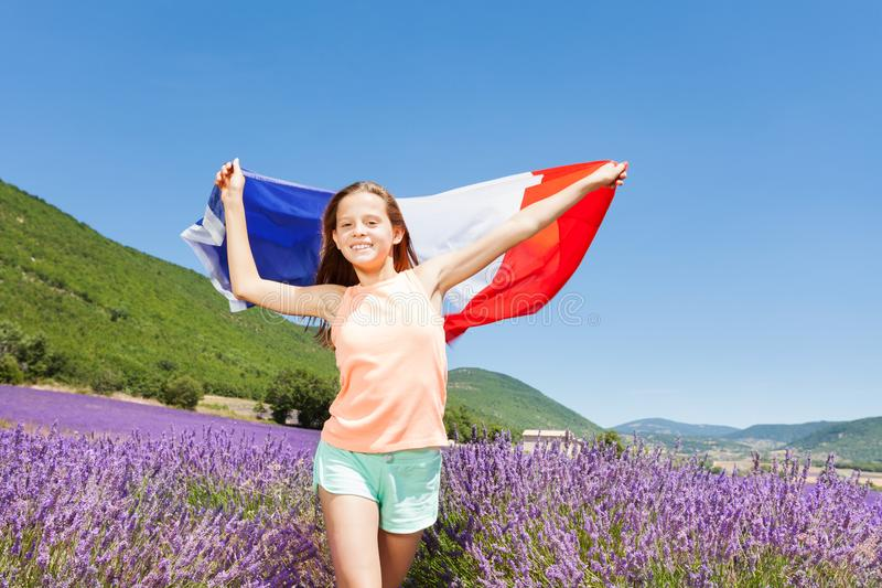 Gelukkig meisje die Franse vlag op lavendelgebied golven royalty-vrije stock afbeeldingen