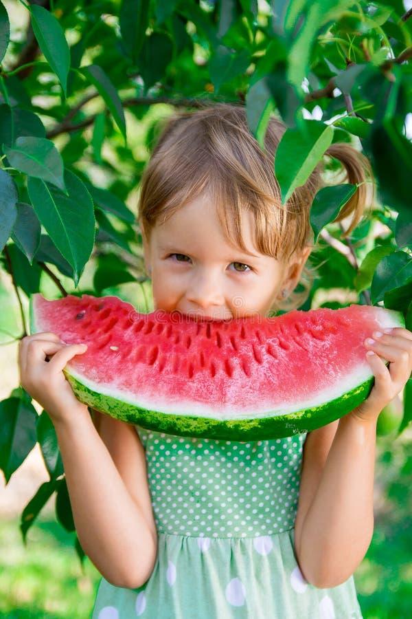 Gelukkig meisje die grote watermeloenplak eten Portret royalty-vrije stock foto