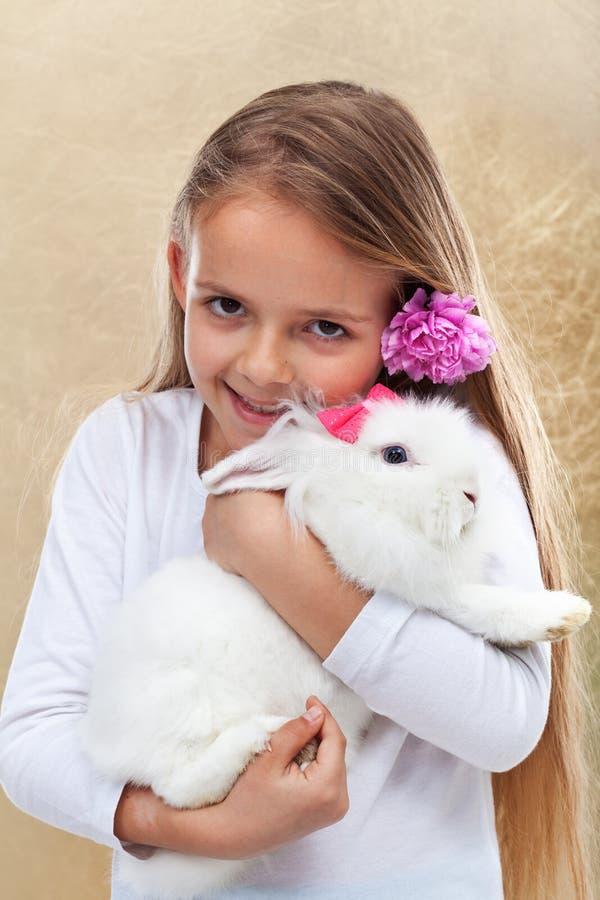 Gelukkig meisje die haar leuk wit konijn houden stock foto's
