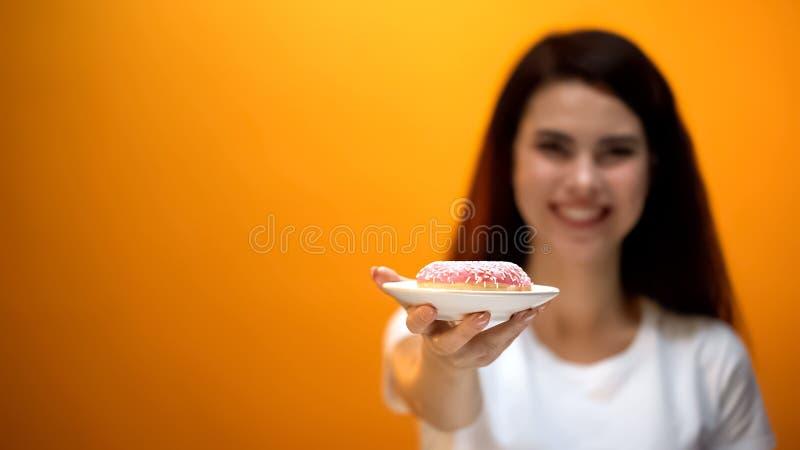 Gelukkig meisje die heerlijke doughnut tonen aan camera, gezoete snack, zwaarlijvigheidsrisico royalty-vrije stock fotografie