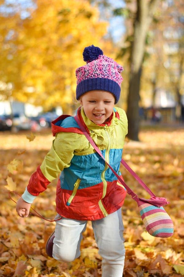 Gelukkig meisje die in heldere kleren met bladeren in een stadspark spelen in de herfst stock foto's