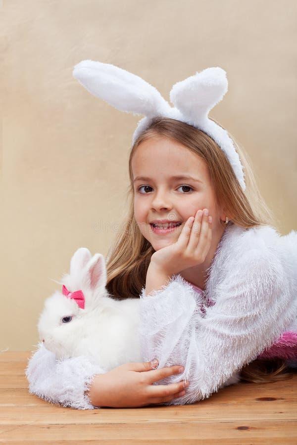 Gelukkig meisje die in konijntjeskostuum haar wit konijn houden stock foto