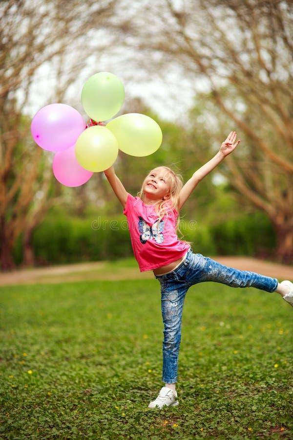Gelukkig meisje die met ballons in stadspark het vieren de versheid van de de zomerlevensstijl van aard springen stock foto