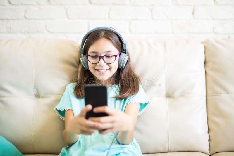 Gelukkig meisje die met bril thuis op comfortabele laag en Li ontspannen stock fotografie