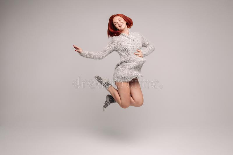 Gelukkig meisje die met gemberhaar in studio met grijze achtergrond springen royalty-vrije stock fotografie