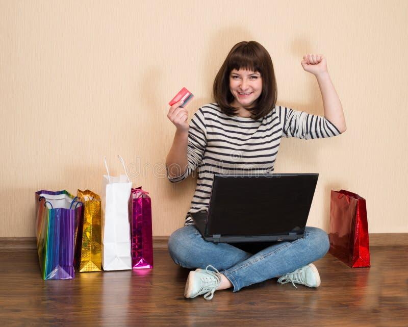 Gelukkig meisje die met het winkelen zakken op de vloer met laptop a zitten royalty-vrije stock afbeelding