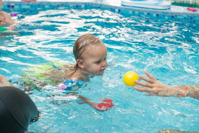 Gelukkig meisje die met poolnoedel leren te zwemmen stock foto