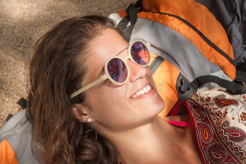 Gelukkig meisje die met rugzak op het de zomerstrand genieten van stock foto