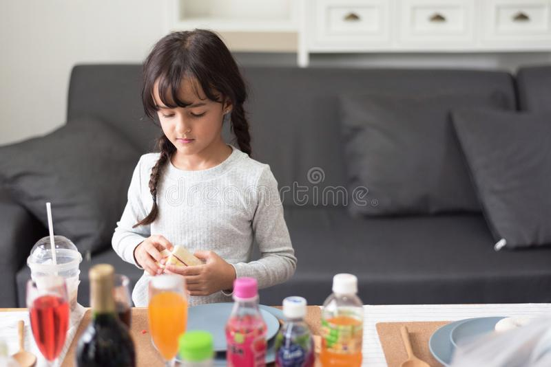 Gelukkig meisje die met stuk speelgoed als chef-kok in woonkamer voorbereidingen treffen te koken Speels van kind en gelukonderwi stock afbeelding