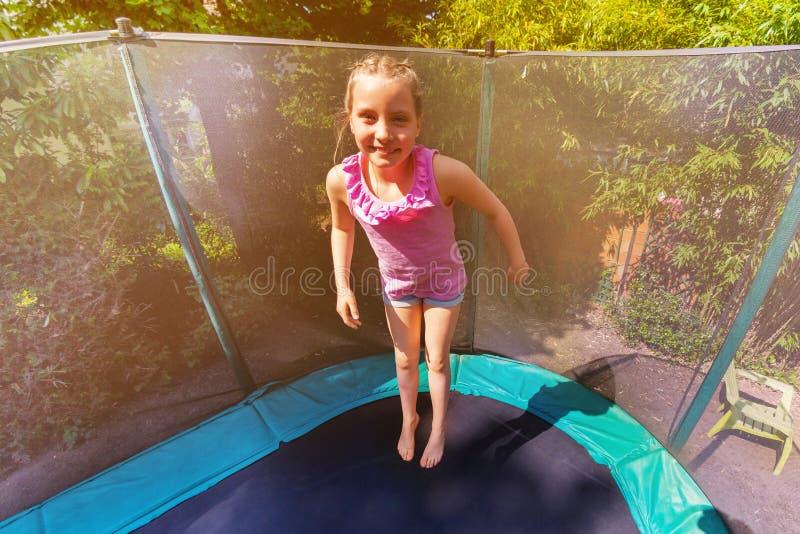 Gelukkig meisje die omhoog op de trampoline in openlucht stuiteren royalty-vrije stock fotografie