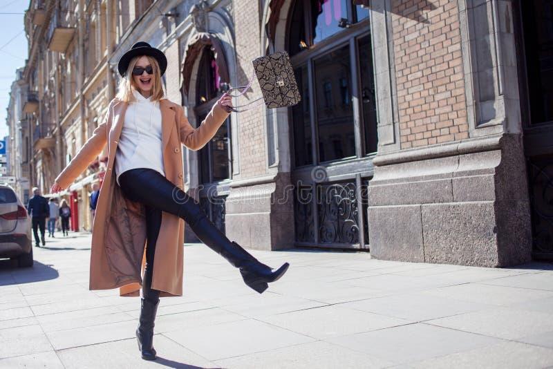 Gelukkig meisje die onderaan de straat, Zonnige dag lopen Modieus en in royalty-vrije stock afbeeldingen