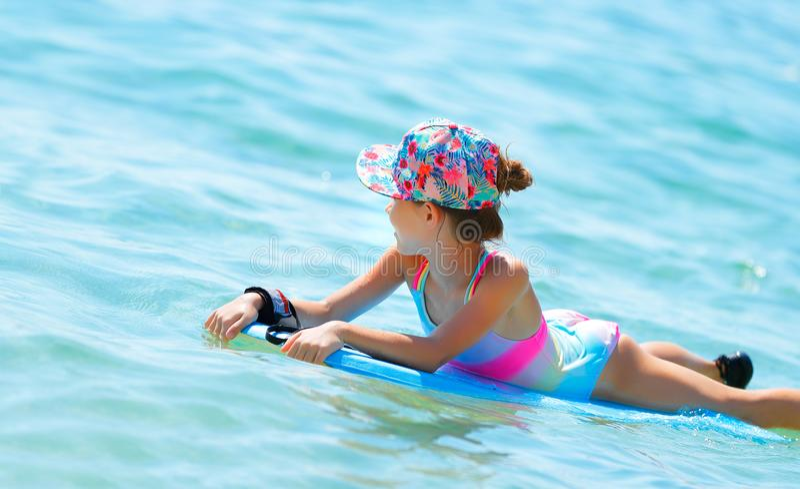 Gelukkig meisje die op bodyboard zwemmen stock afbeeldingen