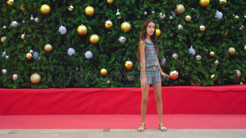 Gelukkig meisje die op de achtergrond van de Kerstboom en de palmen in een tropische stad dansen Het concept Nieuwjaar stock foto