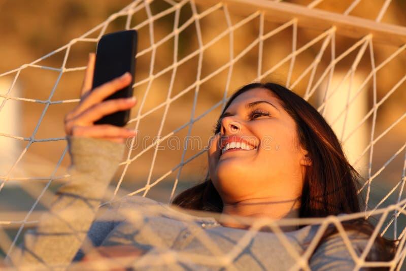 Gelukkig meisje die op een hangmat rusten die een smartphone met behulp van royalty-vrije stock foto