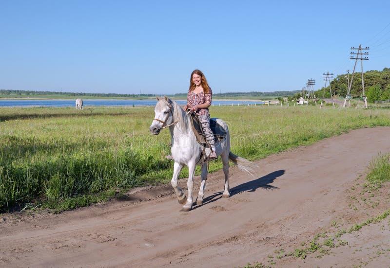Gelukkig meisje die op horseback, op een landelijke weg, tegen de achtergrond van een meer berijden royalty-vrije stock fotografie