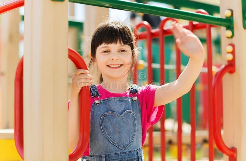 Gelukkig meisje die op kinderenspeelplaats beklimmen stock afbeeldingen
