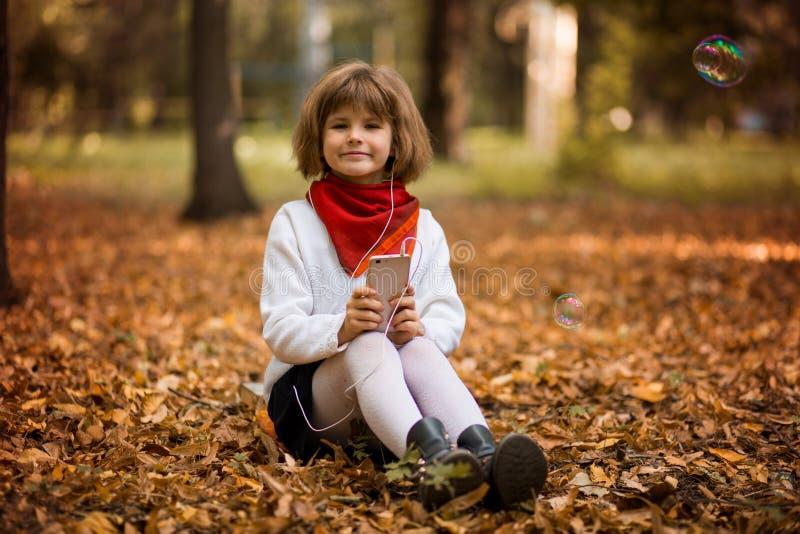 Gelukkig meisje die op smartphone babbelen Mededeling, onderwijs, school, technologie en Internet-concept stock afbeeldingen