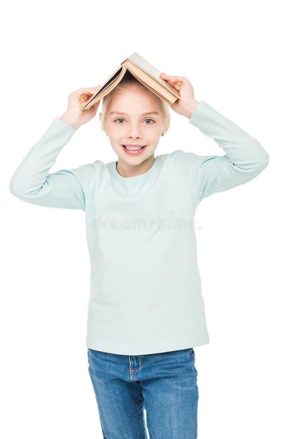 gelukkig meisje die open boek op hoofd houden en bij camera glimlachen stock foto