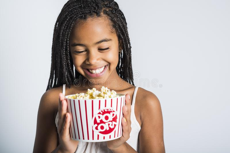 Gelukkig meisje die popcorn over grijze achtergrond eten royalty-vrije stock foto's