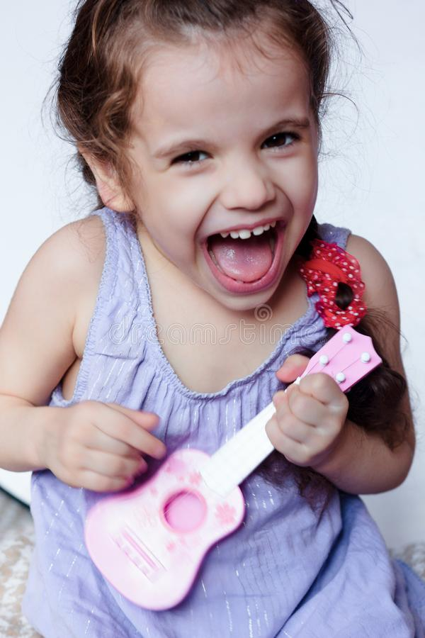 Gelukkig meisje die pret het spelen met stuk speelgoed gitaar of ukelele hebben royalty-vrije stock fotografie