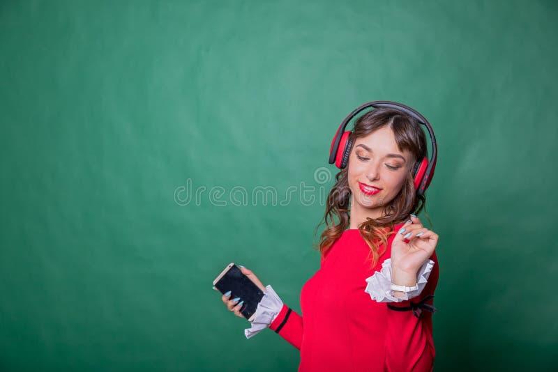 Gelukkig meisje die rode kleding het dansen het zingen en het luisteren muziek online met hoofdtelefoons van een smartphone op gr stock fotografie