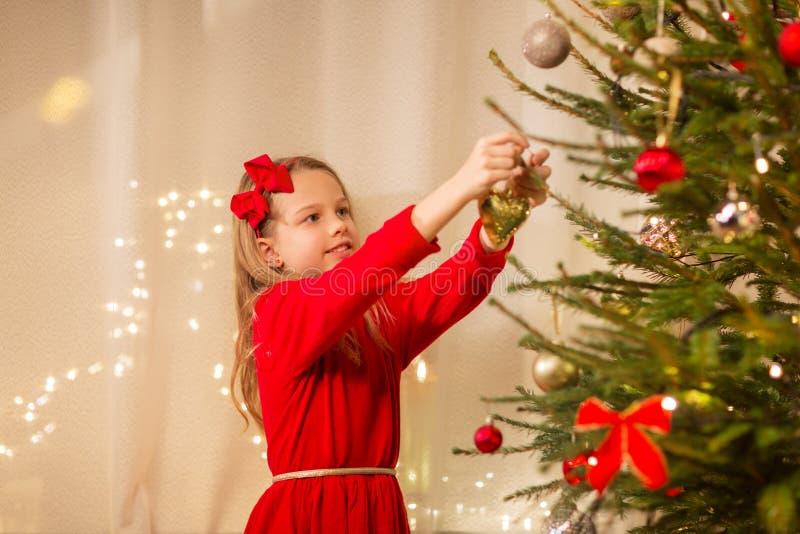 Gelukkig meisje die in rode kleding Kerstmisboom verfraaien stock afbeelding
