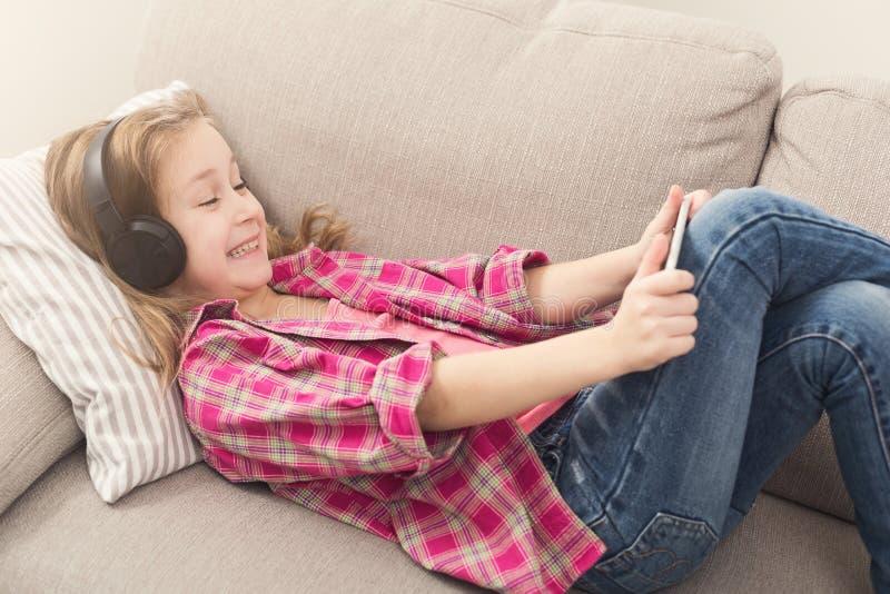 Gelukkig meisje die smartphone op bank thuis gebruiken stock foto's