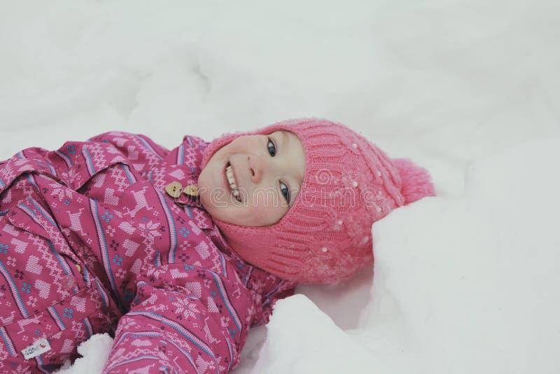 Gelukkig meisje die in sneeuw rollen en pret hebben stock afbeeldingen