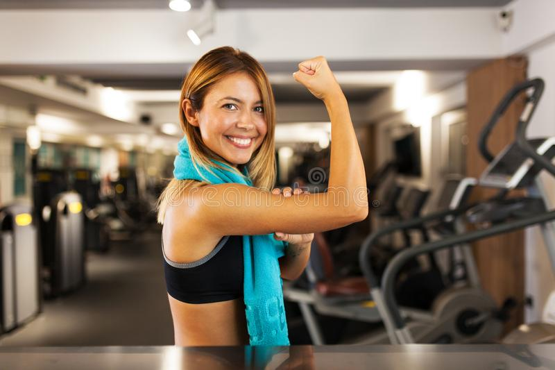 Gelukkig meisje die spieren in een geschiktheidsclub tonen stock fotografie
