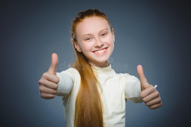 Gelukkig meisje die thubs verschijnen Het kind van het close-upportret glimlachen geïsoleerd op grijs stock afbeeldingen