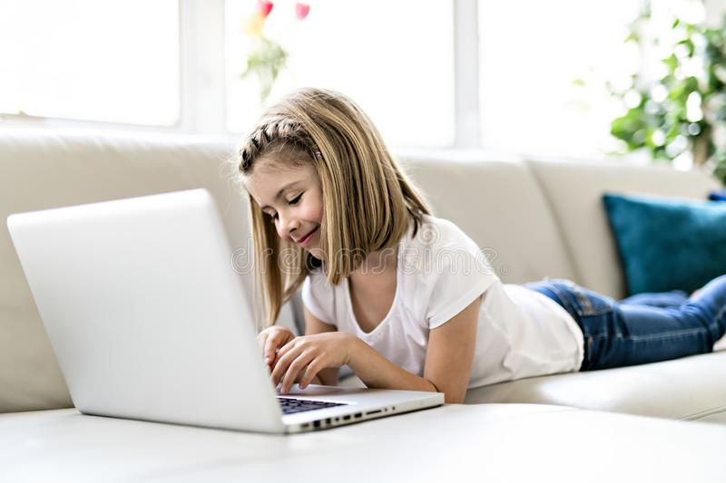 Gelukkig meisje die thuis met laptop aan bank werken stock fotografie