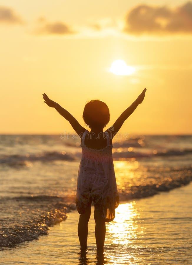 Gelukkig meisje die zich op het strand bevinden stock fotografie