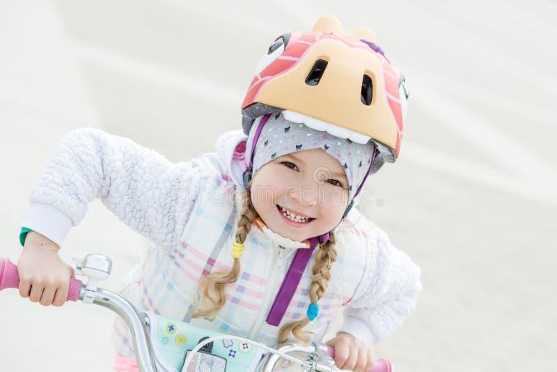 Gelukkig meisje in een helm op een fiets royalty-vrije stock afbeeldingen