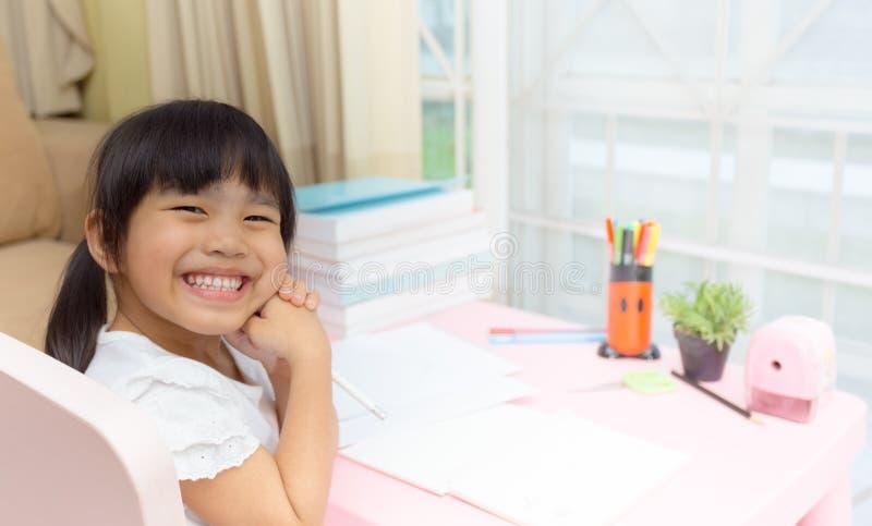 Gelukkig meisje en vroeg onderwijs kleine jonge geitjes die zijn thuiswerk voor pret en het leren doen royalty-vrije stock afbeeldingen
